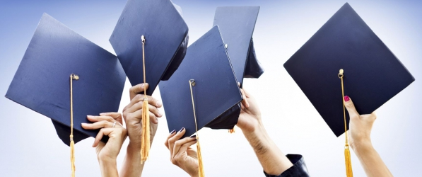 hands in the air holding mortarboards, raised in celebration